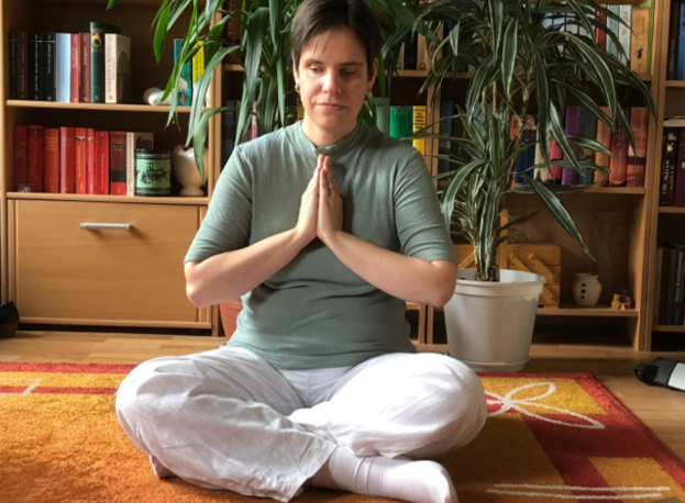 Lady sat on floor indoors with legs crossed in meditation pose.